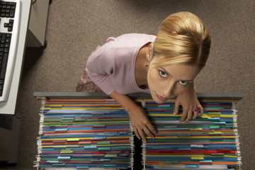 Portrait of a businesswoman searching a file in a filing cabinet drawer