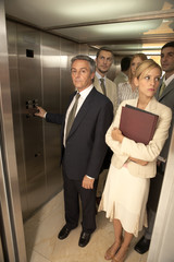 Five business executives in an elevator