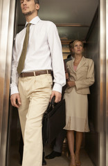 Businessman exiting from an elevator with a businesswoman standing behind him
