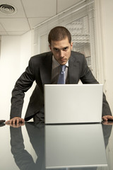 Portrait of a businessman standing in front of a laptop