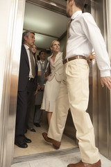 Side view of a businessman entering an elevator with four business executives in it