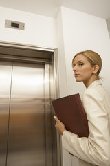 Side view of a businesswoman standing in front of an elevator