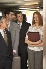 Three businessmen looking at a businesswoman standing in an elevator