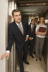 Portrait of a businessman looking outside of an elevator with his colleagues standing behind him