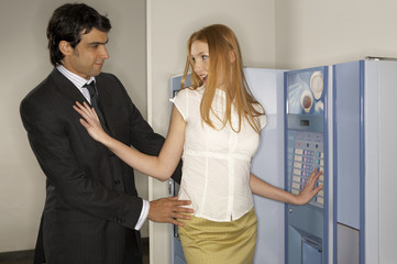 Businessman touching the waist of a businesswoman in front of a vending machine