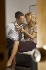 Businessman and a businesswoman flirting in an office