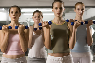 Four young women exercising with dumbbells in a gym