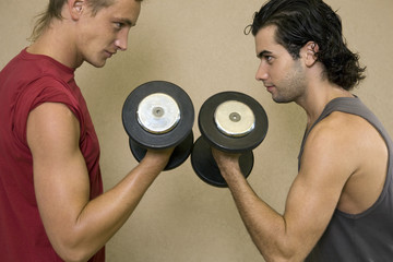 Side profile of two young men exercising with dumbbells