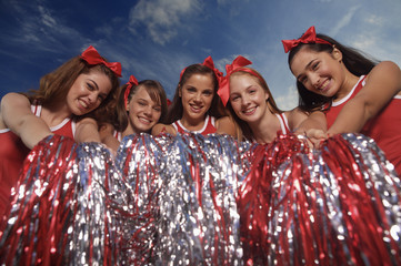 Portrait of five cheerleaders holding pom-poms and smiling