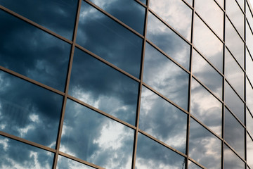 wall glass skyscraper with reflection of the sky at night