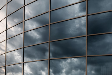Glass skyscraper wall with reflection of dark stormy clouds at s
