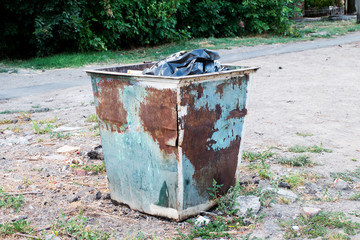 Trash can standing outdoors. Trash dumpster in ghetto neigborhoo
