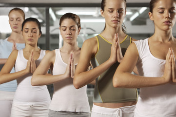 Five young women doing yoga in a gym