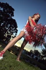 Low angle view of a cheerleader holding pom-poms and smiling