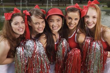 Portrait of five cheerleaders smiling