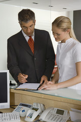 Mid adult man filling a form with a nurse standing beside him