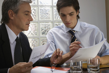 Two businessmen sitting at a desk and looking at documents in an office