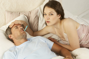 Mid adult woman measuring the temperature of a mid adult man with a thermometer