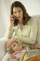 Mid adult woman talking on a mobile phone with her daughter lying on her lap