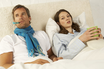 Portrait of a mid adult woman reclining with a mid adult man on the bed and holding a cup of tea