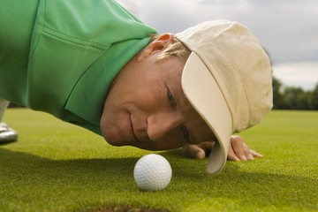 Close-up of a mid adult man judging a golf ball on a golf course