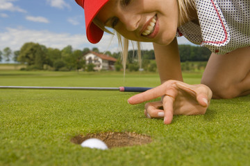 Close-up of a mid adult woman putting a golf ball into a hole