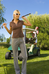 Mid adult woman standing on a golf course and holding a golf club and smiling