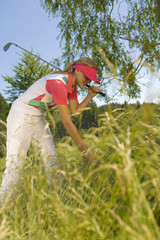 Side profile of a mid adult woman searching a golf ball in bush