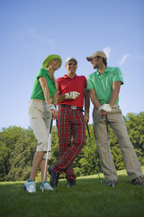 Two mid adult men standing with a mid adult woman on a golf course and holding golf clubs