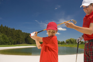 Side profile of a boy swinging a golf club with his father standing beside him