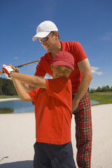 Mid adult man giving golf training to his son