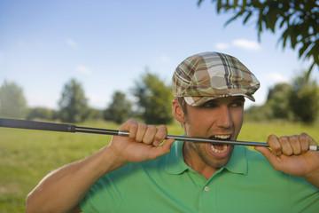 Close-up of a mid adult man biting a golf club