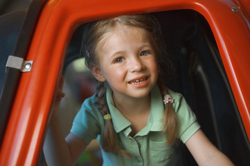 Portrait of a girl smiling in a toy helicopter