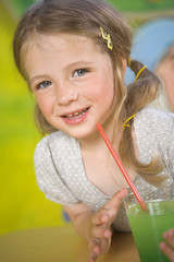 Portrait of a girl holding a glass of smoothie and smiling