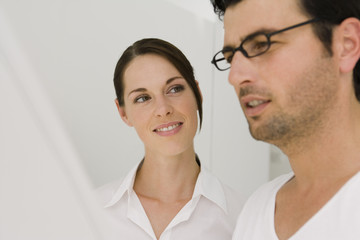 Close-up of a businessman looking at a blueprint with a businesswoman smiling