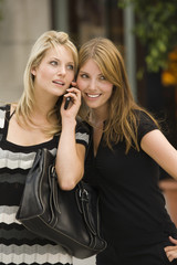 Young women listening to cell phone together
