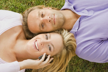 Portrait of a young woman lying on the grass with a young man and talking on a mobile phone