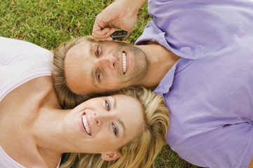 Portrait of a young man talking on a mobile phone and lying on the grass with a young woman