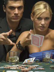 Couple throwing playing cards at poker game