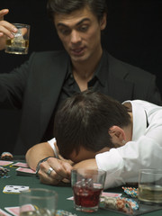 Upset man with head down at poker game