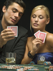 Couple looking at playing cards at poker game