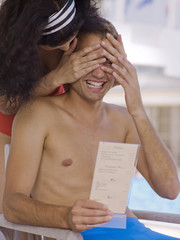 Woman covering man's eyes near pool