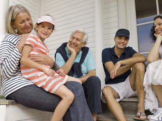 Three generation family sitting on veranda