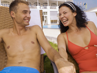 Couple laughing near poolside