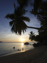 People on beach at sunset, Anse a la Mouche, Mahe', Seychelles