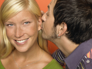Man kissing the ear of young woman