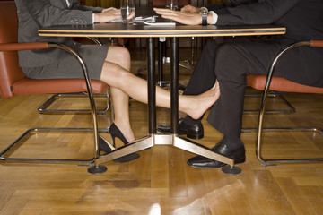 Businesspeople playing footsie under table