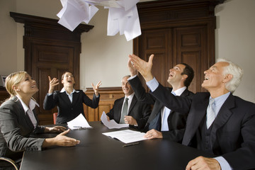 Businesspeople throwing papers in the air