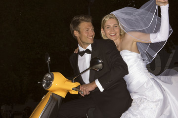 Newlywed couple riding a motor scooter and smiling