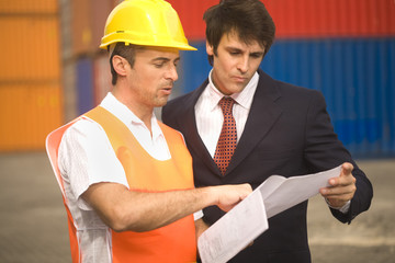 Male dock worker showing a document paper to a businessman